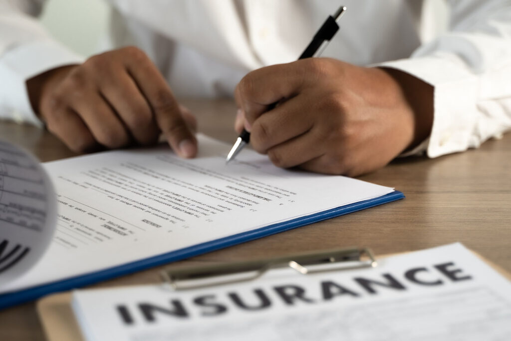 closeup of a person signing an insurance document