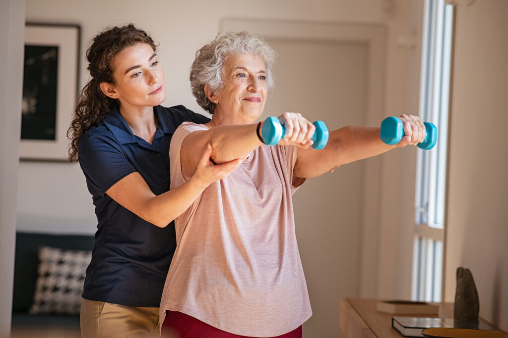 Therapist assisting senior woman with exercises in home.