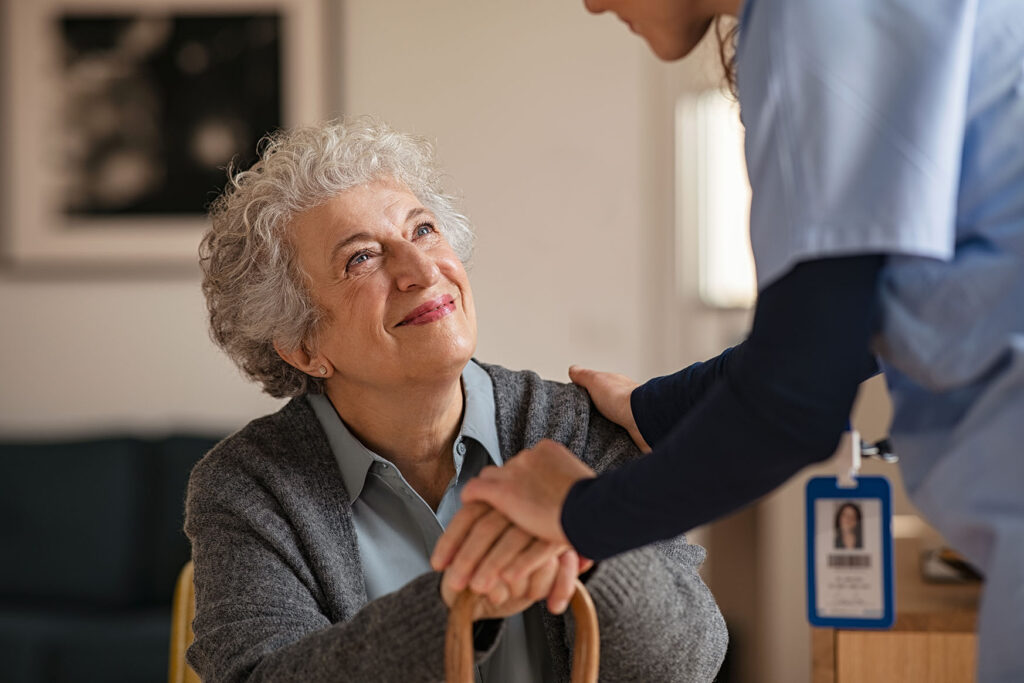 Smiling senior woman talking to her general practitioner visiting her at home